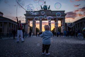 Mann macht Seifenblasen für kleines Kind, das vor dem Brandenburger Tor in Berlin steht.