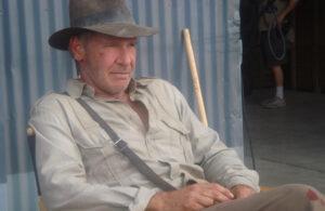 Harrisson Ford bei den Dreharbeiten zu Indiana Jones und das Königreich des Kristallschädels in Kostüm auf einem Stuhl sitzend.