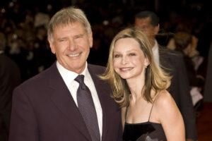Harrison Ford und Calista Flockhart stehen lächelnd nebeneinander in Abendkleidung.